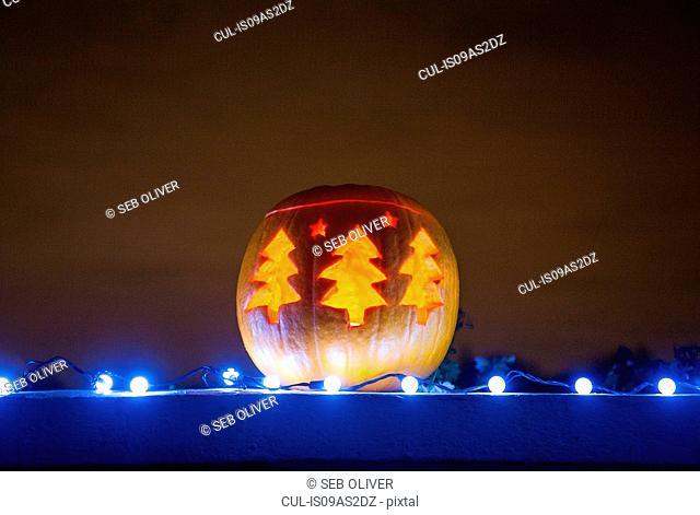 Pumpkin with Christmas trees carved into it
