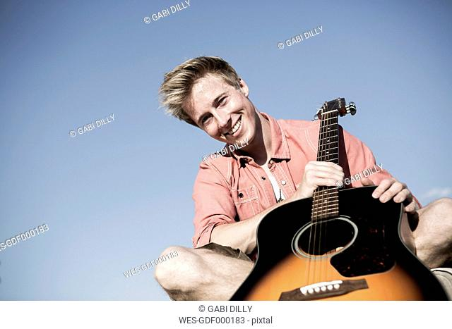 Germany, Young man holding guitar, smiling