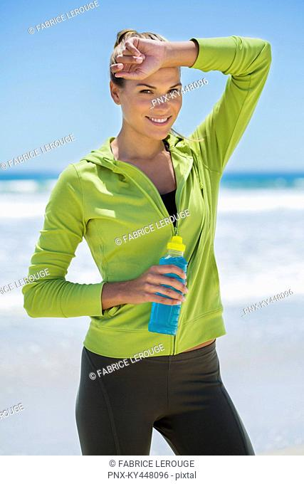 Smiling woman holding a water bottle on the beach