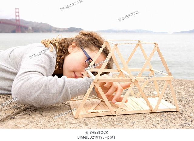 Caucasian girl examining project on wall over ocean