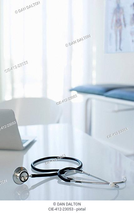 Stethoscope and laptop on white desk in doctors office