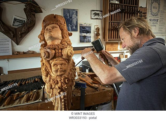A craftsman, carver working on a carving with a mallet and small chisel marking the wood and adding texture and shape. A wooden female ship's figurehead