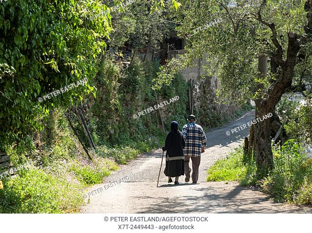 Elderly Greek couple walking in a country lane, Exohori village, Outer Mani, Peloponnese, Greece