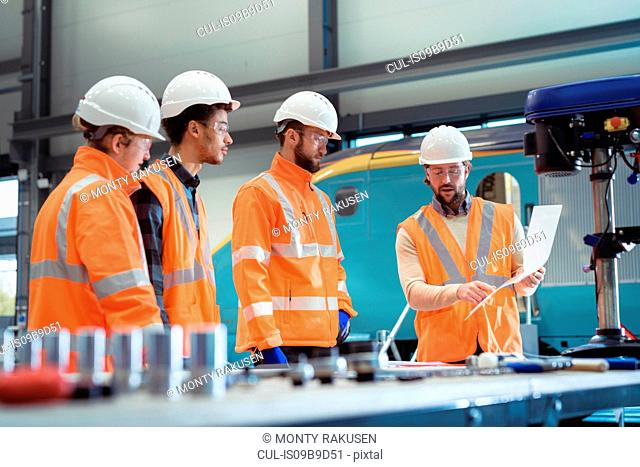 Group of apprentices with instructor at railway engineering facility