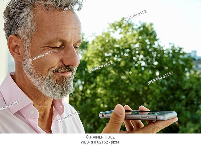 Portrait of smiling mature man holding smartphone outdoors