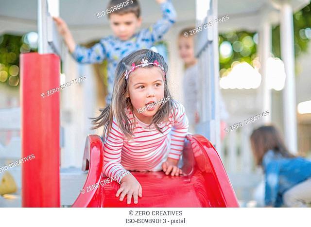 Girl at preschool, lying at top of playground slide in garden