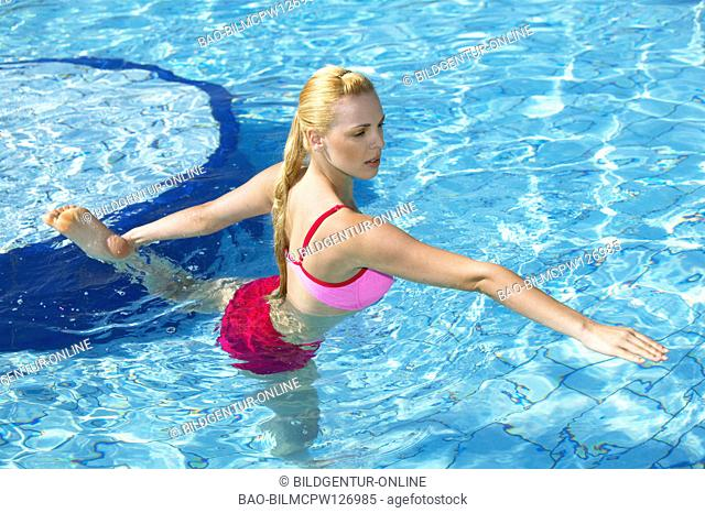 young woman doing acqua gymnastics in the swimmingpool