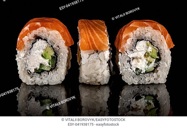 Three pieces of sushi rolls Philadelphia. Black background. Reflection