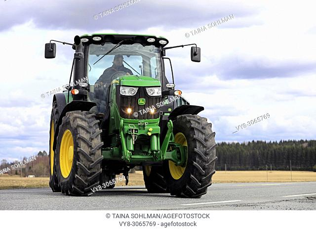 Farmer makes a right turn with John Deere 6150R tractor and agricultural trailer off main road. Jokioinen, Finland - April 30, 2018
