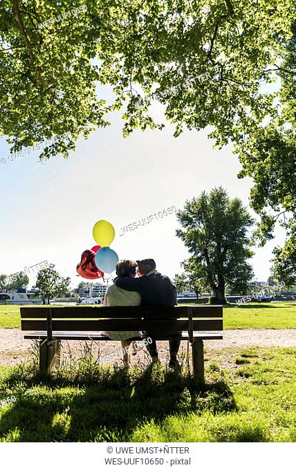 Happy senior couple with balloons kissing on bench in a park