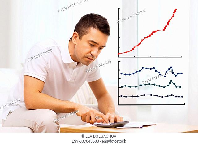 business, savings, finances and people concept - man with papers and calculator at home