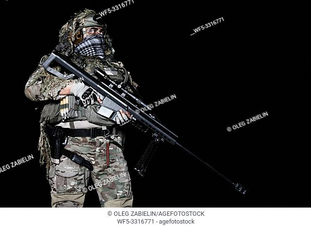 Army sniper with big rifle standing on black background
