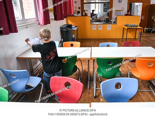 07 August 2019, Berlin: A student wipes the table after lunch in the cafeteria of the primary school at Wuhlheide. Photo: Jens Kalaene/dpa-Zentralbild/ZB
