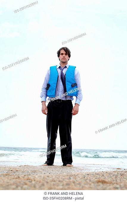 Businessman wearing life jacket on beach
