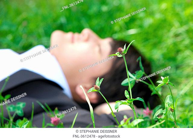 Young businessman lying in meadow