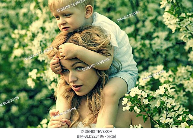 Caucasian mother holding son near flowers in tree