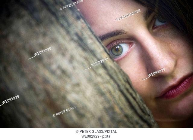 Close-up of a young woman behind a tree