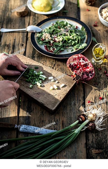 Preparing green salad with pomegranate, manna croup and spring onion, chopping spring onion