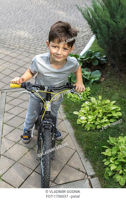 High angle portrait of boy riding bicycle on street by plants