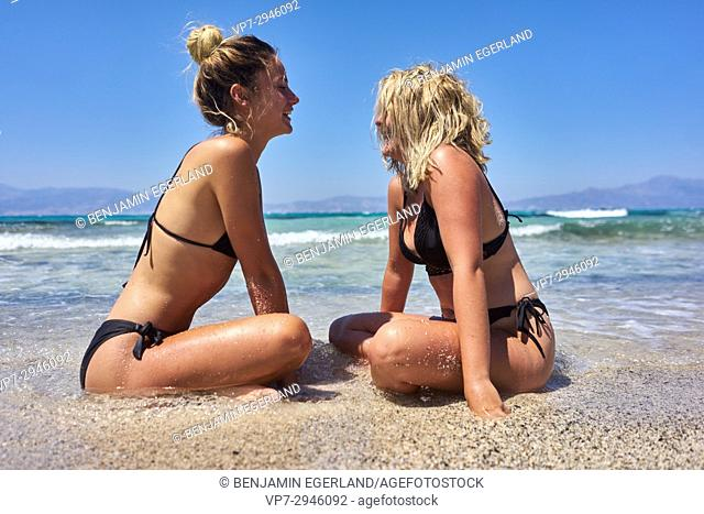 two happy young women sitting together on the beach. Dutch ethnicity. At holiday destination Chrissi Island, Crete, Greece