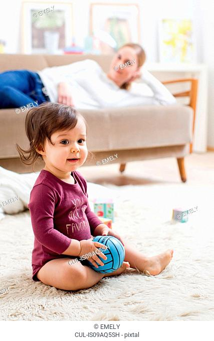Mother lying on sofa watching baby boy play on floor