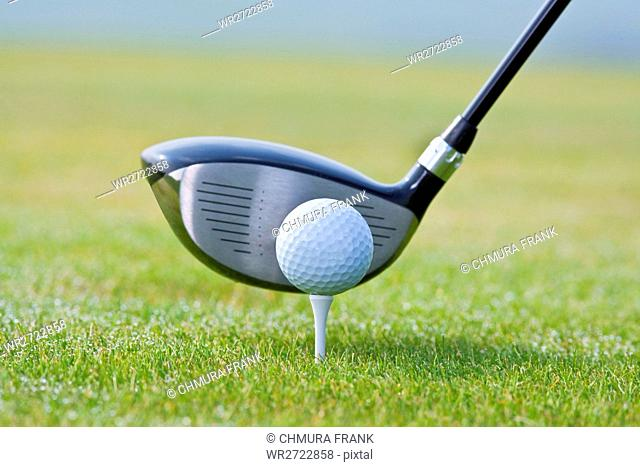 closeup of a golf ball and club on green grass - club out of focus