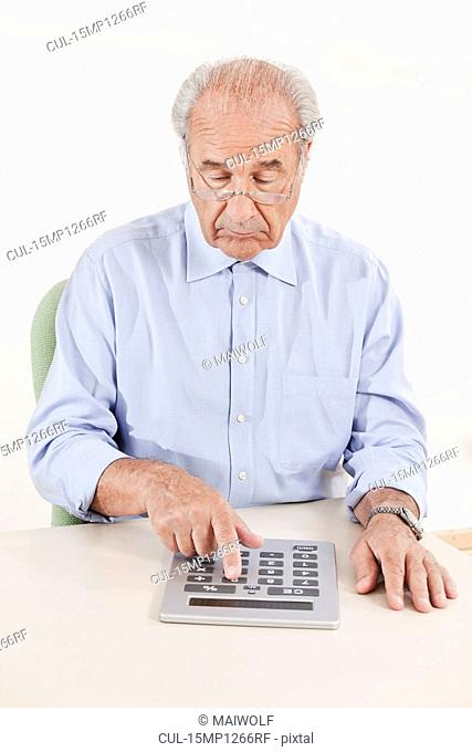 Senior typing on a huge calculator