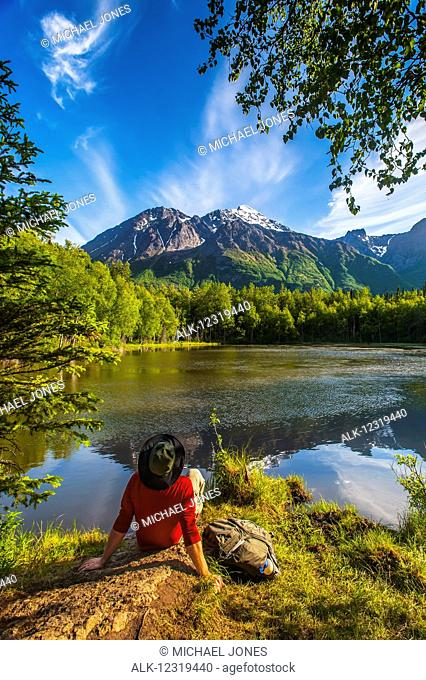 Hiker resting next to Dew Pond in the Chugach State Park near Eagle River, Southcentral Alaska, summer
