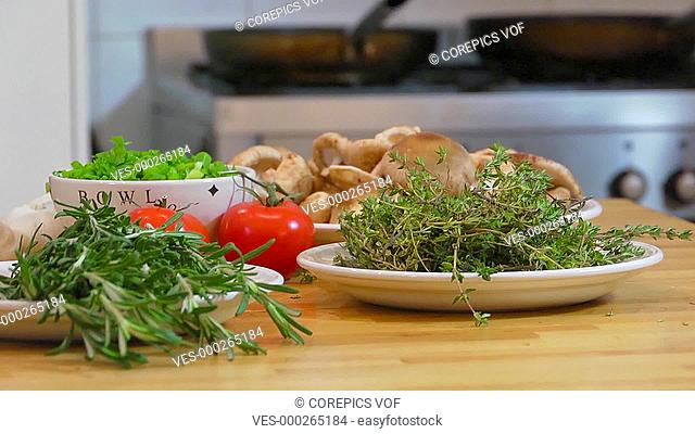 Pan over various bowls and dishes with herbs, spices and other ingredients, ending at a chef, choping up thyme on a cutting board