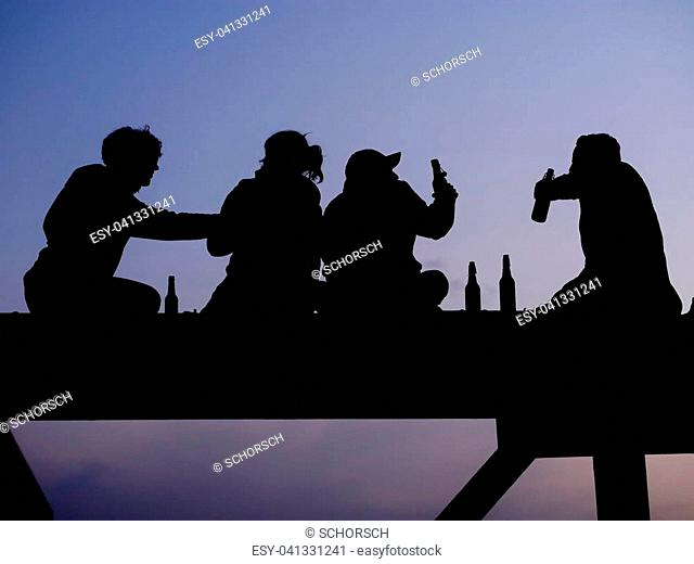Silhouette of four friend drinking beer