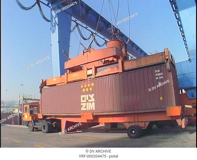 A crane lifts a large cargo container from the back of a flatbed truck