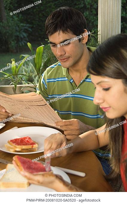 Woman having breakfast while a man reading a newspaper, New Delhi, India