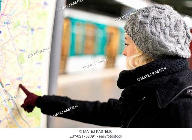 Lady looking on public transport map panel