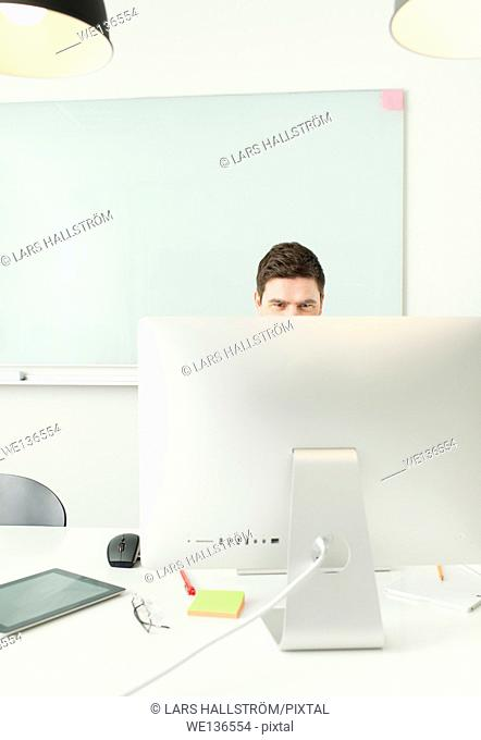 Businessman sitting by desk, working with computer in office