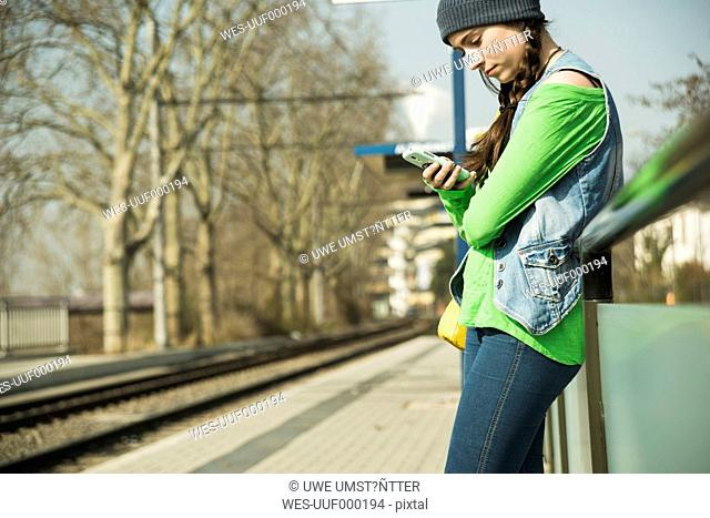 Teenage girl using smartphone at platform
