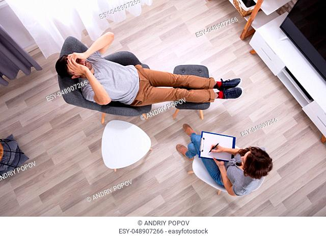 Female Psychologist With Clipboard Sitting Near Young Man Suffering From Depression