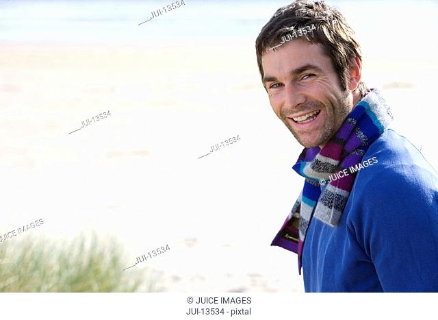 Man standing on beach, smiling, portrait