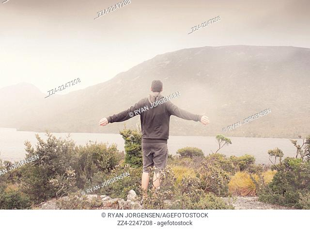 Man expressing the joy in winter freedom with arms stretched out on a misty mountainous lake landscape. Taken Cradle Mountain, Tasmania, Australia