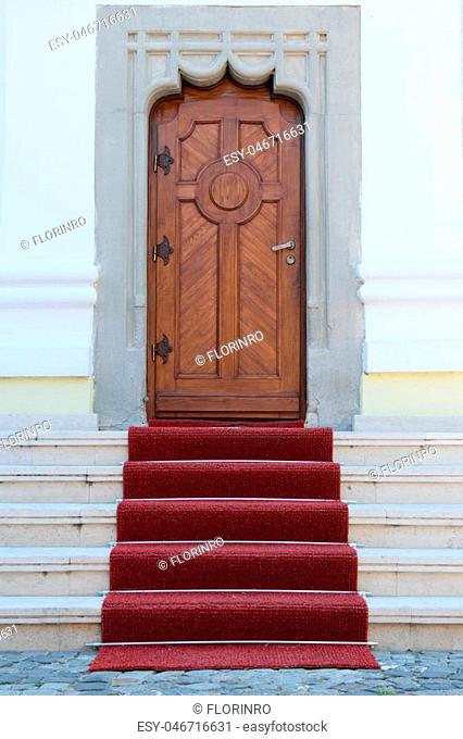 massive wood door, artistic concrete walls and red carpet on stairs entrance