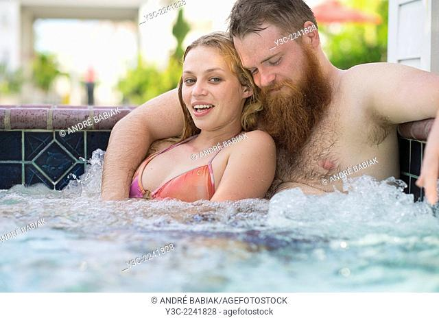 Young woman and bearded man enjoying a bath in a hot tub pool
