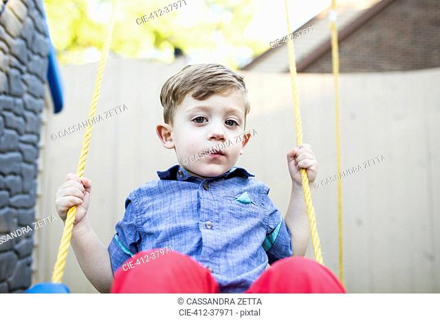 Portrait serious preschool boy swinging on swing