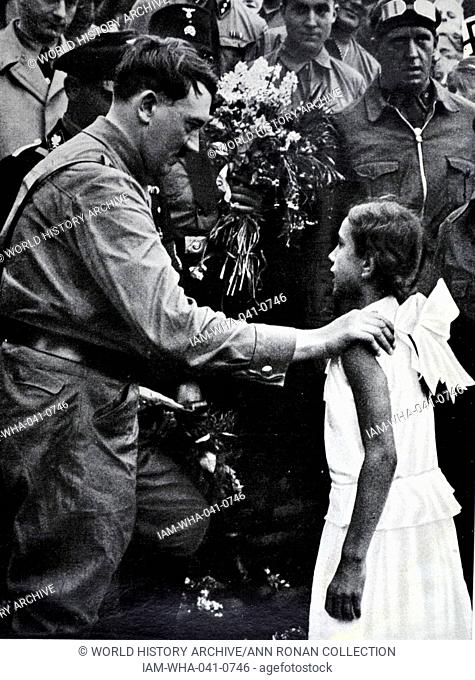 Adolf Hitler 1889-1945. German politician and the leader of the Nazi Party, greeted by Hitler Youth as Baldur von Schirach looks on