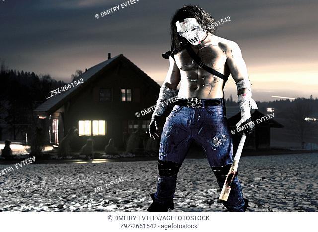 Costumed hero as a street maniac with a bat. Casey Jones in Alps. Combined image - studio work was added to real landscape
