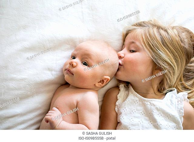 Overhead view of young girl and baby brother lying on bed, girl kissing baby brother
