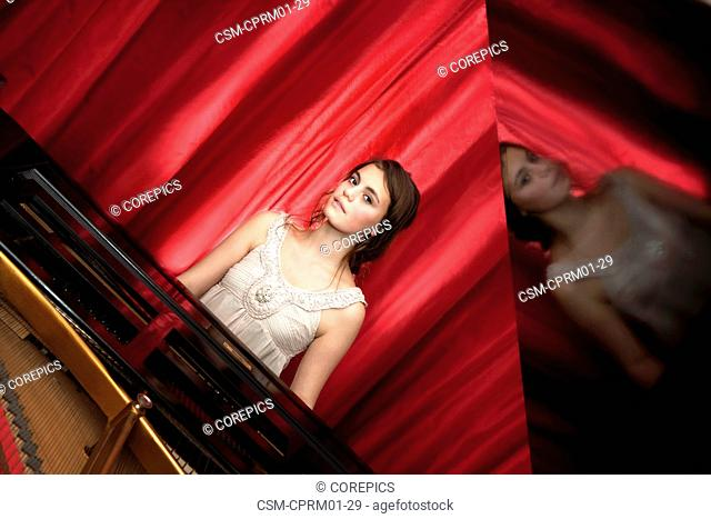 Young, talented, girl playing on a grand piano with the lid open