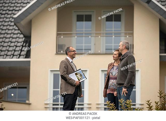 Estate agent communicating with potential buyers in front of residential house