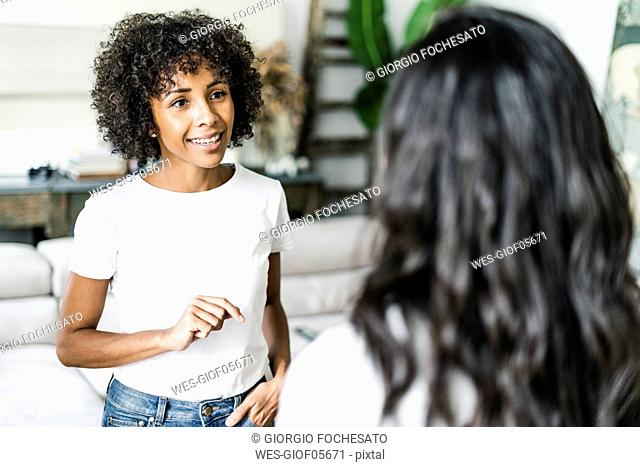 Portrait of smiling woman talking to a friend at home