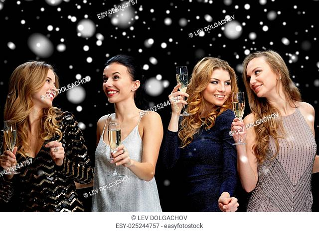 new year party, christmas, winter holidays and people concept - happy women with champagne glasses and dancing over black background with snow