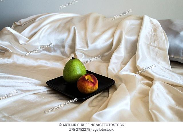Partial view of a bed with a small plate of fruit