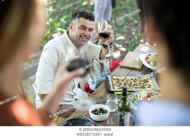 Friends and family having lunch in garden with red wine